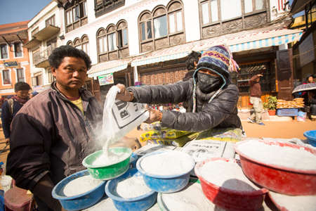 KHATMANDU, NEPAL - DEC 17: Unidentified man sell cement for donations for repairs near stupa Boudhanath during festive solemn Puja of H.H. Drubwang Padma Norbu Rinpoches reincarnations, Dec 17, 2013 in Khatmandu, Nepal.