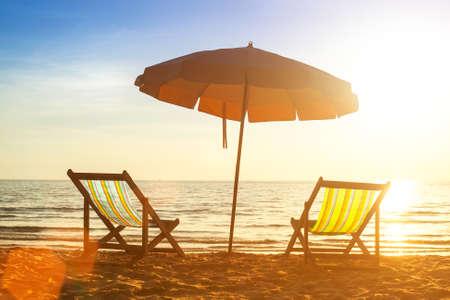 loungers: Beach loungers on deserted coast sea at sunrise. Stock Photo