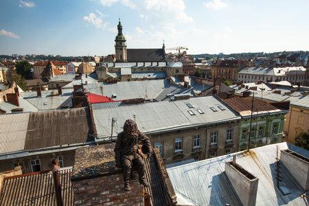 judged: LVIV, UKRAINE - AUG 6: Chimneysweep monument is on the roof of a historic building House of Legends on Aug 6, 2012 in Lviv, Ukraine. On 2009 Ukr. magazine Focus judged Lviv best Ukrainian city to live Editorial