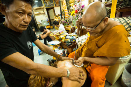 practiced: NAKHON CHAI, THAILAND - MAR 1: Unidentified monk makes traditional Yantra tattooing on Mar 1, 2012 in Nakhon Chai, Thailand. Yantra tattoo also called Sak Yant, practiced in Southeast Asian countries.