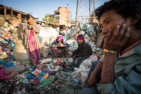 poorer: KATHMANDU, NEPAL - DEC 22, 2013: Unidentified people from poorer areas working in sorting of plastic on the dump. Only 35% of population have access to adequate sanitation.