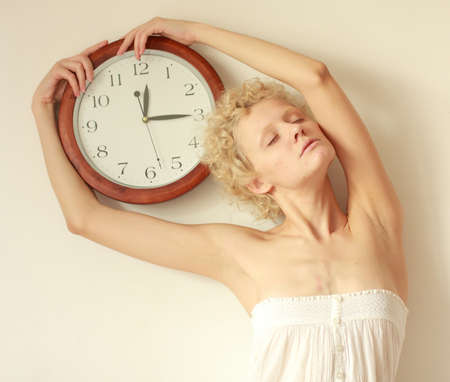 scrawny: The sleepy - young scrawny girl with big clock in hands