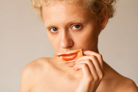 Conceptual image about plastic surgery lips - beautiful young girl closes her lips painted a picture with lips. photo