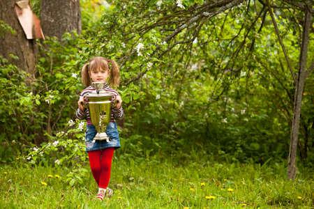 Little girl and Russian Samovar in the garden. photo