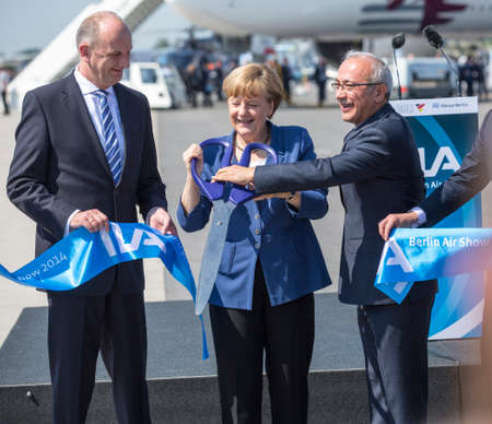 chancellor: BERLIN, GERMANY - MAY 20, 2014: German Chancellor Angela Merkel (C), Turkish Minister of transport Lutfi Elvan (R) open up the International aviation and space exhibition ILA.