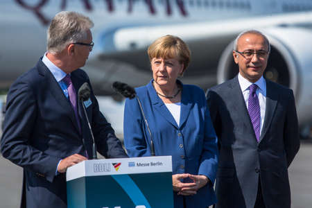 chancellor: BERLIN, GERMANY - MAY 20, 2014: German Chancellor Angela Merkel (C) and Turkish Minister of transport Lutfi Elvan (R) open up the International aviation and space exhibition ILA. Editorial