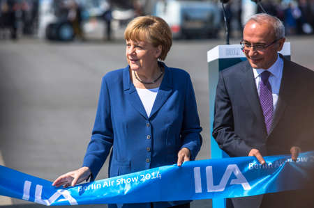 chancellor: BERLIN, GERMANY - MAY 20, 2014: German Chancellor Angela Merkel (L) and Turkish Minister of transport Lutfi Elvan (R) open up the International aviation and space exhibition ILA.