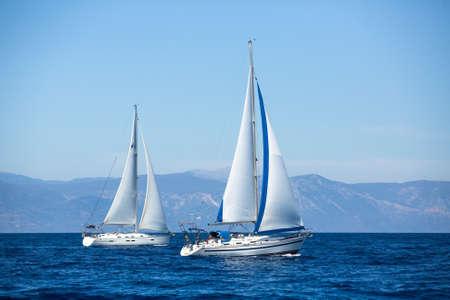 poros: Group of sail yachts in regatta near a coast. Stock Photo