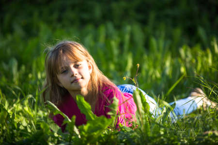 Portrait of nice little girl lying in the grass outdoors. photo