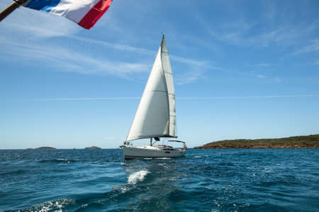 maneuvering: Beautiful yacht in the light-blue sea, fresh wind and pleasant movement.