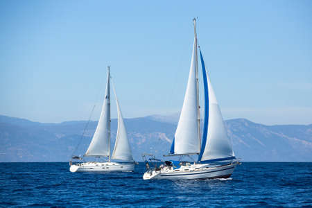 sailboat race: Two sailboats on peaceful still waters in a harbor. Stock Photo