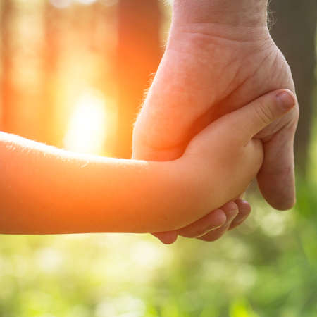 hold hands: Hands, father with his son close-up, outdoors. Stock Photo