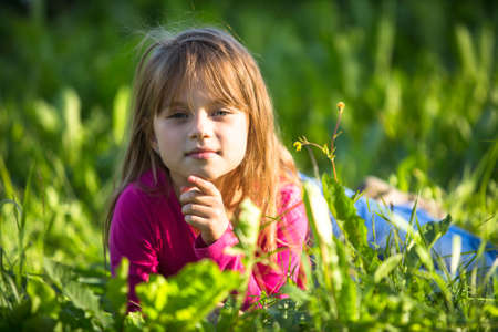 Portrait of little girl lying in the grass. photo