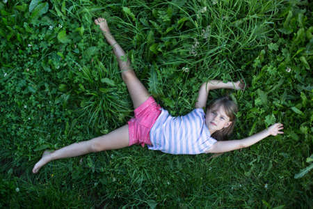 Little cute girl lying on the grass, top view.