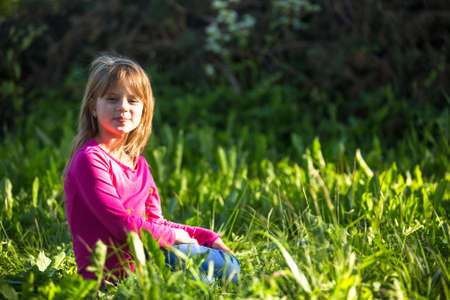 Portrait of little girl in the grass outdoors. photo
