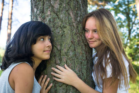 Two teen-girl playing on grass in the park.  photo