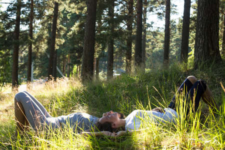 Two young girl lying on grass in the park. photo