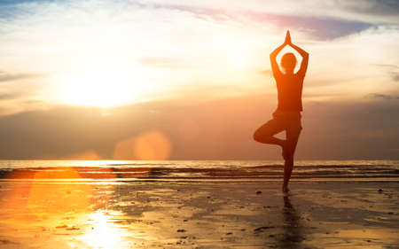 yoga silhouette: Silhouette young female practicing yoga on the beach at sunset.