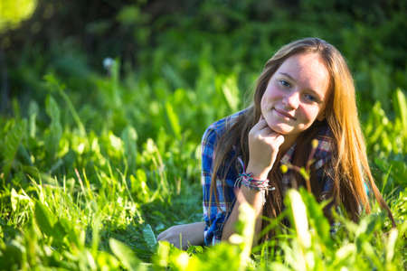 Portrait of teen-girl lying in the grass. photo