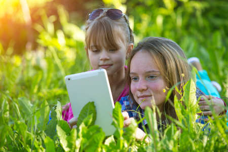 Young sisters with a tablet PC, lying in the grass. photo