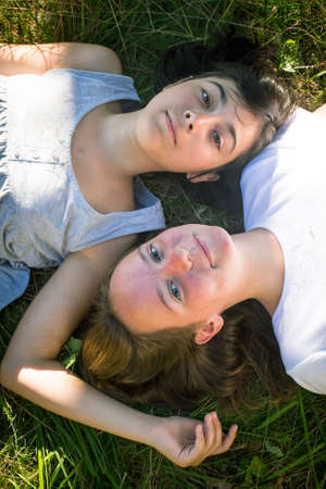 Two young girl lying on grass having good time. (top view) photo