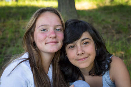 Two young girl sitting on grass in the park.  photo