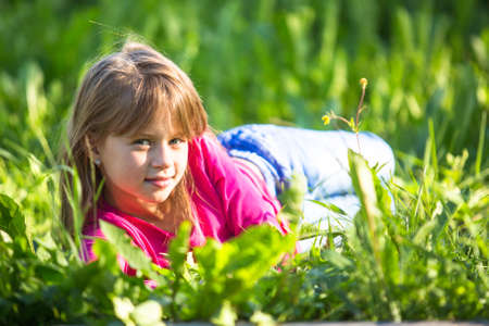 Little girl lying in the grass. photo