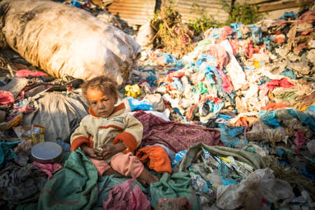 developing country: KATHMANDU, NEPAL - DEC 22, 2013: Unidentified child is sitting while her parents are working on dump. In Nepal annually die 50,000 children, in 60% of cases - malnutrition. Editorial