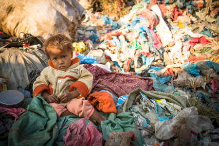 KATHMANDU, NEPAL - DEC 22, 2013: Unidentified child is sitting while her parents are working on dump. In Nepal annually die 50,000 children, in 60% of cases - malnutrition. Redactioneel