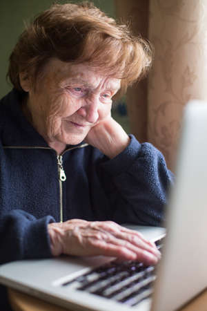 Old woman working on the computer. photo