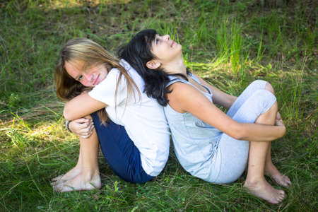 Two young girls playing on grass in the park.  photo