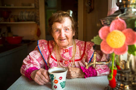 Elderly woman in ethnic clothes drinking tea in his house. photo
