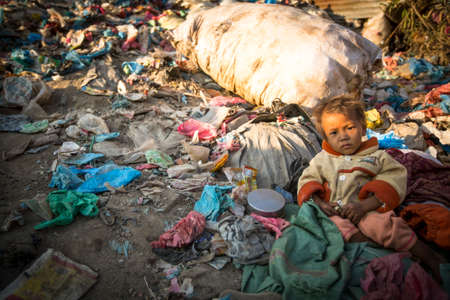 street child: KATHMANDU, NEPAL - DEC 22, 2013: Unidentified child is sitting while her parents are working on dump. In Nepal annually die 50,000 children, in 60% of cases - malnutrition. Editorial
