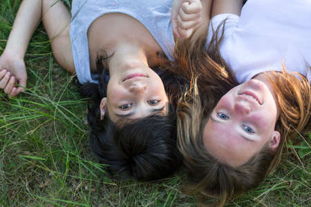 Two young girl lying on grass. photo