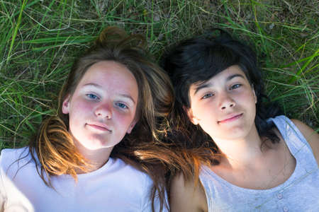 Two young girl lying on grass having good time. photo