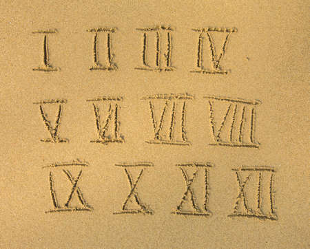 Roman numbers on a sandy beach. photo
