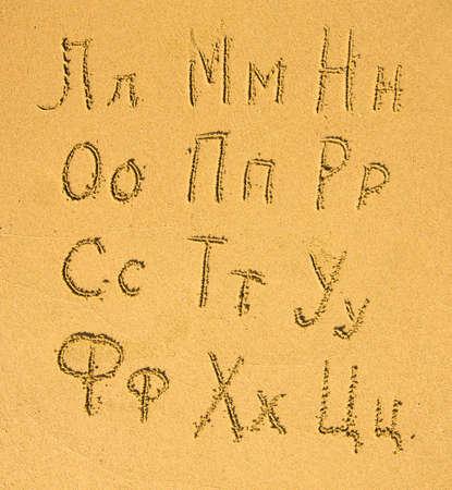 Russian alphabet (23) written on a sand beach. photo