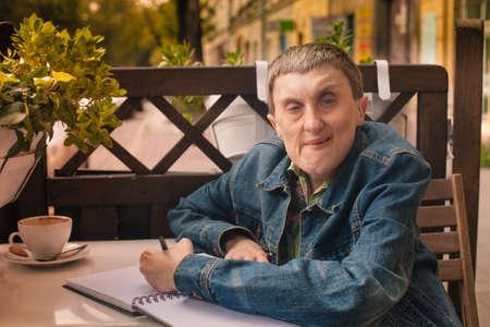 Behinderte Menschen schriftlich in einem Notebook sitzen in einem Straßencafé. Standard-Bild