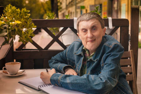 Disabled man writing in a notebook sitting at an outdoor cafe.