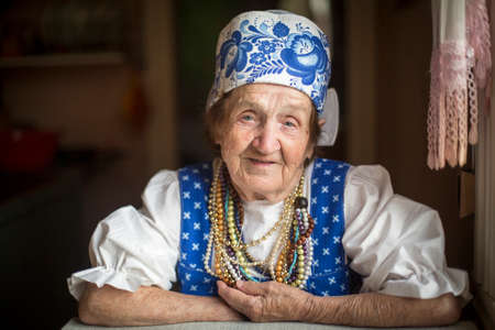 Portrait of elderly woman in ethnic clothes in his house. photo