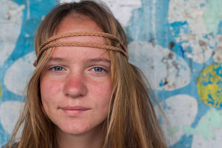 Closeup portrait of young girl hippie, dirty background (concept 70s)