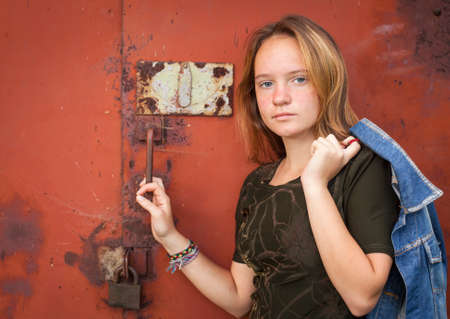 Portrait of cute young girl with a denim jacket on a background of metall walls. photo