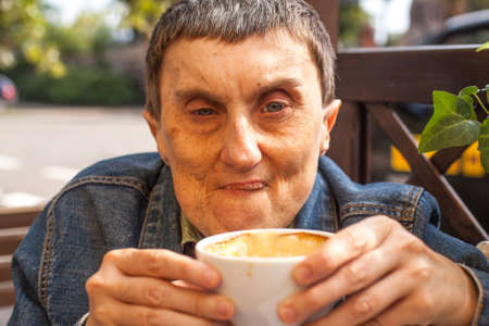 cerebral palsy: Closeup portrait of elderly disabled man with cerebral palsy, at an outdoor cafe. Stock Photo