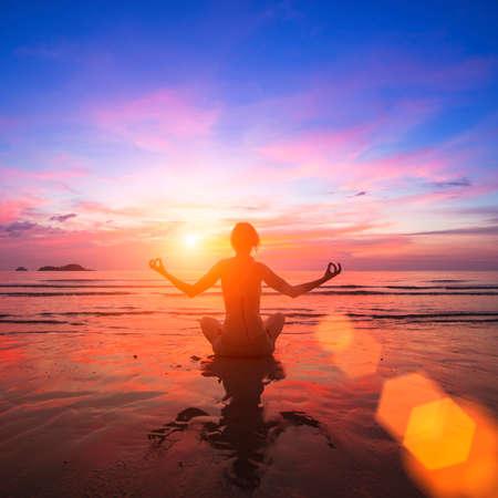 Mädchen praktizieren Yoga auf der Meerseite, die Silhouette in den Strahlen der atemberaubenden Sonnenuntergang.