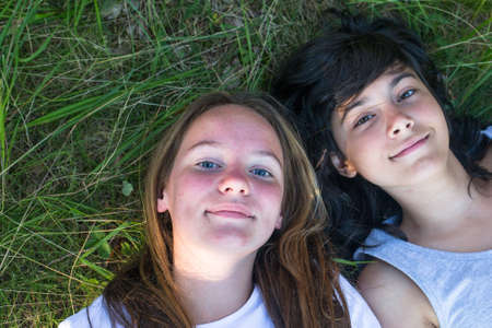 Two young girls lying on the grass, face closeup. Best friends. photo