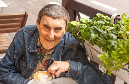 Elderly disabled man with cerebral palsy, smiling sitting at an outdoor cafe. photo