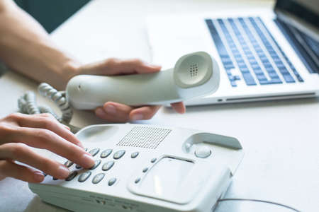 Women's hands dial the number on the telephone, a laptop in the background. Stockfoto