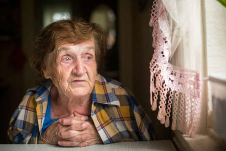 depressed woman: Old woman sitting at a table in his house, with a worried expression on his face.