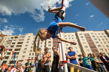 TIKHVIN, RUSSIA - JULY 7, 2014: Unidentified participants city competitions in Street workout timed to the celebration of the day of the city of Tikhvin.