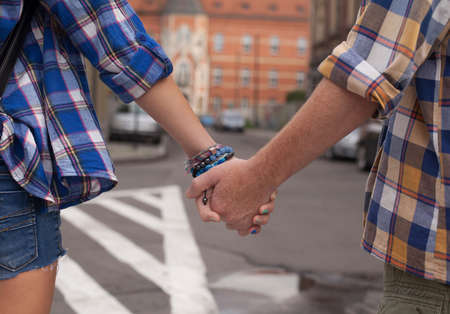europe closeup: Hands of young couple on the street in Europe, close-up shoot. Stock Photo